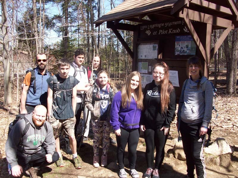 Kids and adults ready to go for hike next to trailhead sign