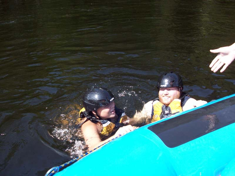 Kid and adult swimming next to raft