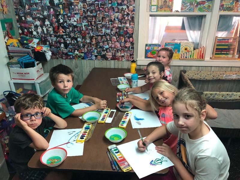 Amorak Kindness Klub with kids around table