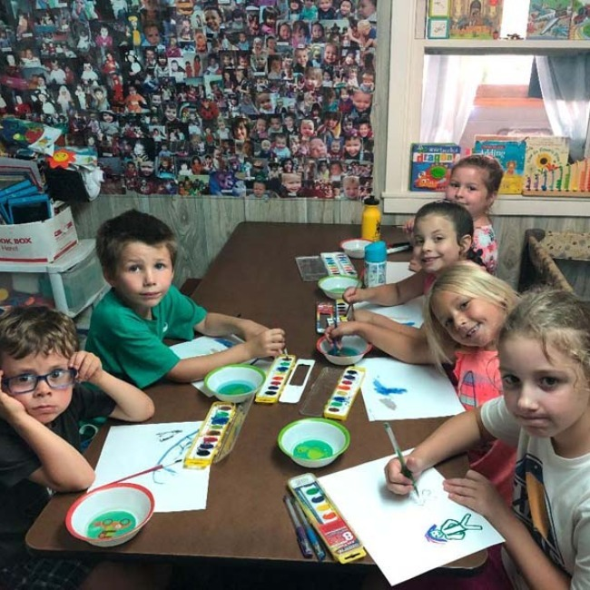 children painting pictures with water color paint
