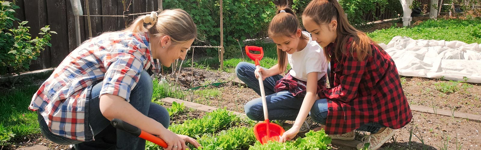 2 teens and women using shovels in garden